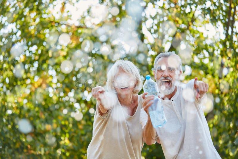 Lachende Senioren spritzen glücklich Wasser stockbild