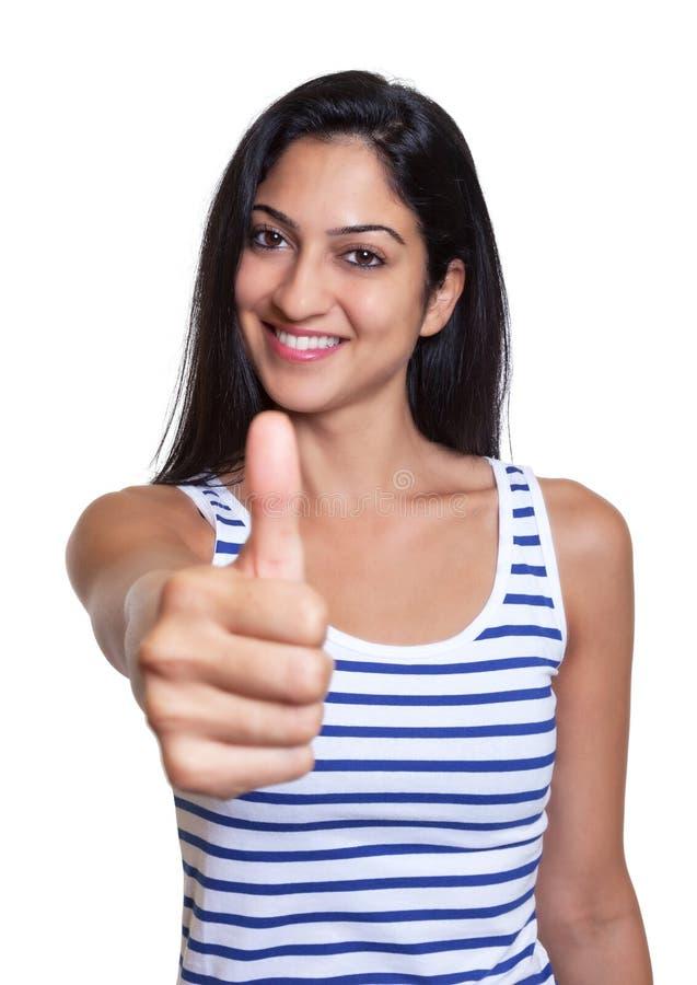 Lachende Turkse vrouw in een gestreept overhemd die duim tonen stock foto