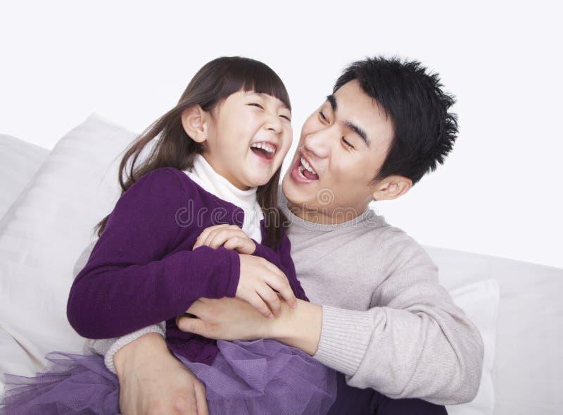 Lachende vader die dochter kietelen en op de bank, studioschot plakken royalty-vrije stock afbeeldingen