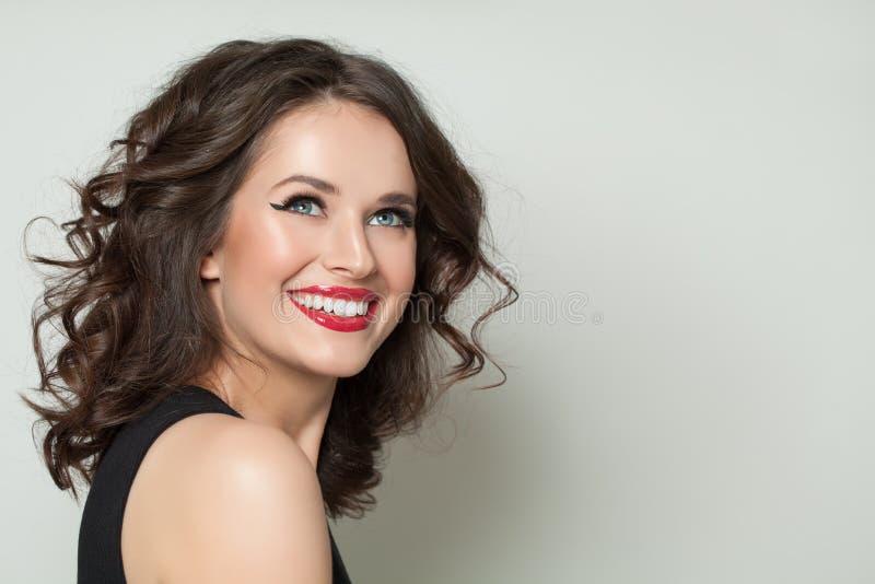 Lachende vorbildliche Frau mit Make-up und gesundes gelocktes Haar auf weißem Hintergrund stockbild