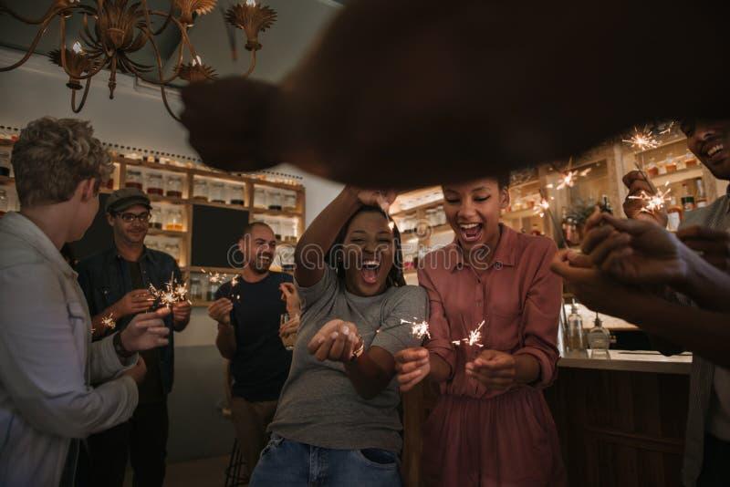 Lachende vrienden die met sterretjes samen in een bar vieren stock foto