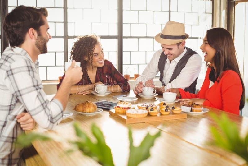 Lachende vrienden die van koffie en traktaties genieten stock foto
