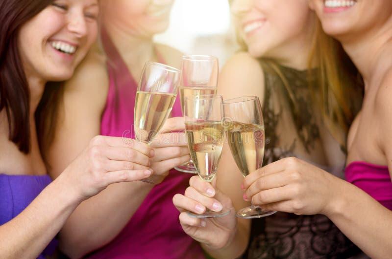Lachende vrolijke jonge vrouwen die samen roosteren royalty-vrije stock foto