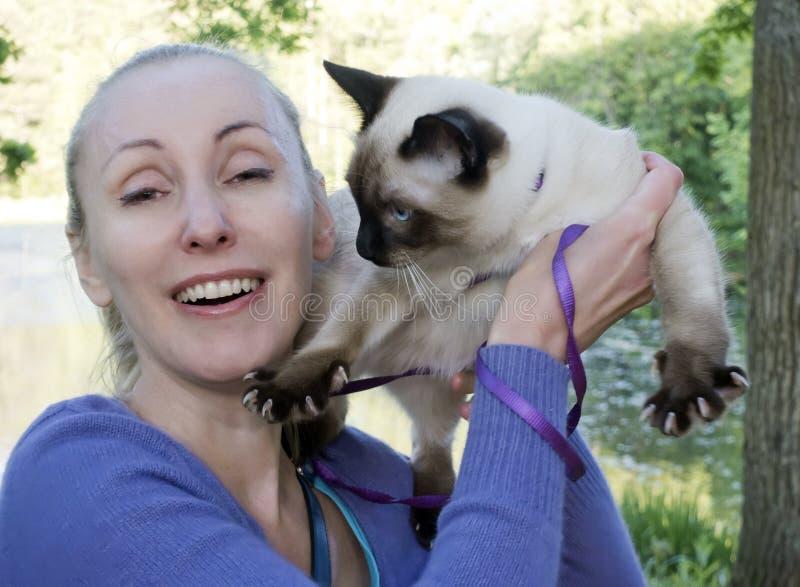 Lachende vrouw die een jonge kat in haar wapens in een de zomerpark houden stock afbeelding