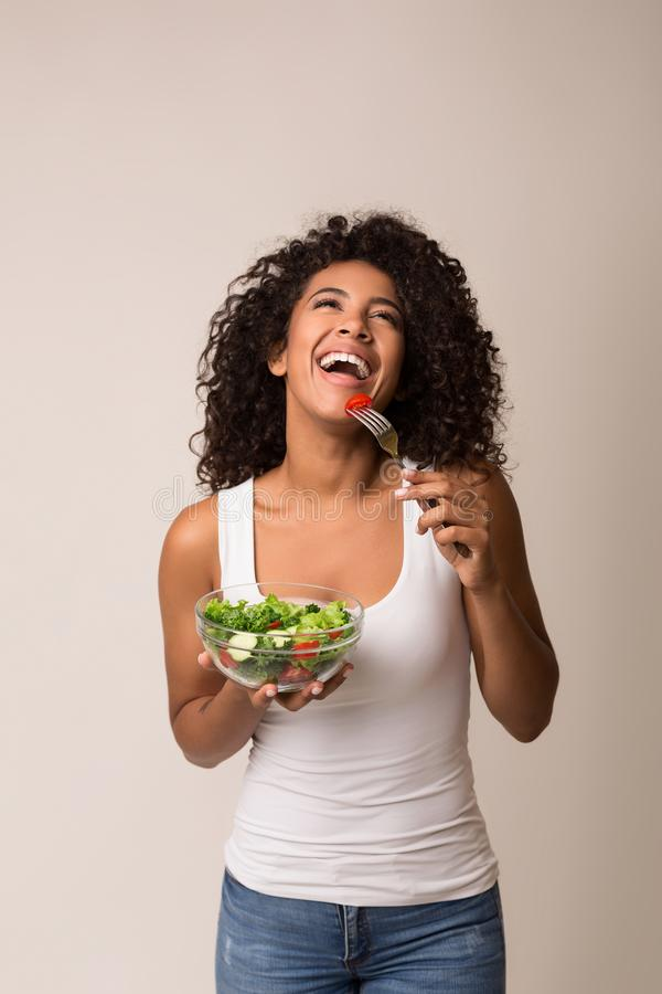 Lachende vrouw die gezonde salade over lichte achtergrond eten stock afbeeldingen