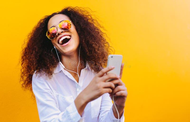 Lachende vrouw die het luisteren van muziek genieten stock afbeeldingen