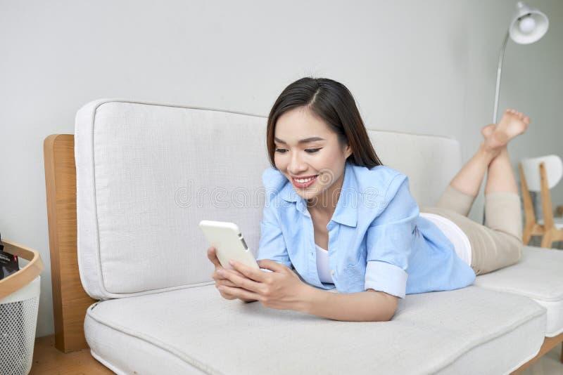 Lachende vrouw die op bank liggen en telefoon bekijken royalty-vrije stock foto's
