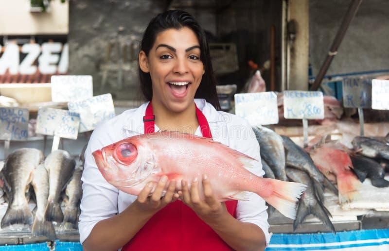 Lachende vrouw die verse vissen op een Latijnse vissenmarkt verkopen stock foto's