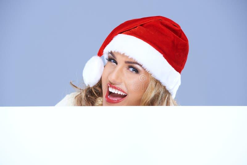 Lachende vrouw in een Kerstmanhoed met teken stock fotografie