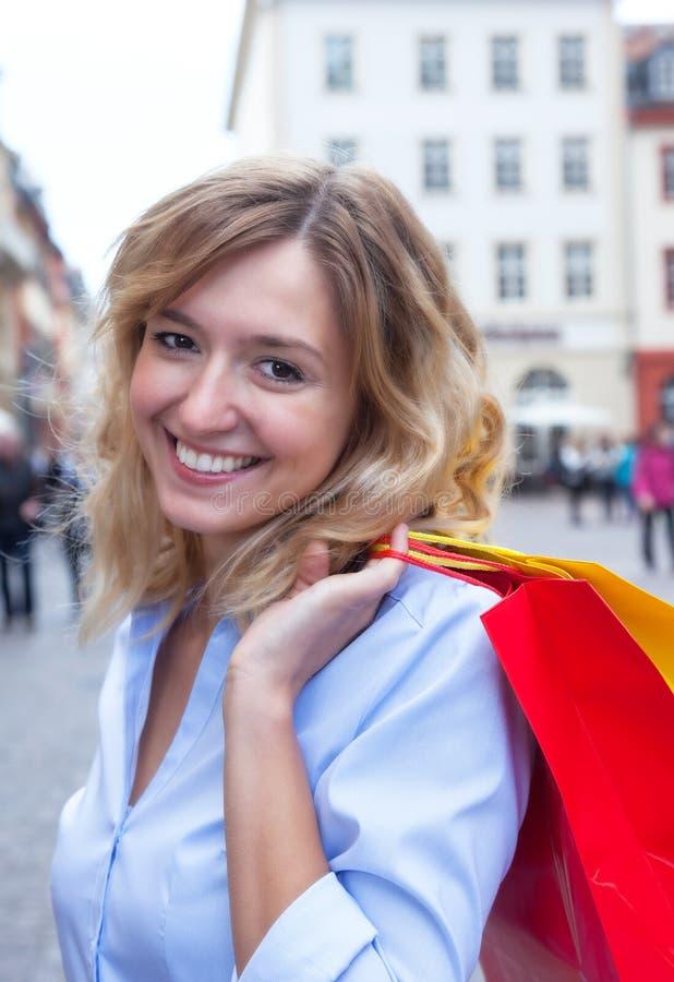 Lachende vrouw met krullende blonde haar en het winkelen zakken in de stad royalty-vrije stock afbeeldingen