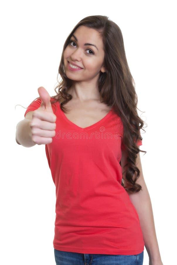 Lachende vrouw met lang donker haar en rood overhemd die duim tonen royalty-vrije stock foto