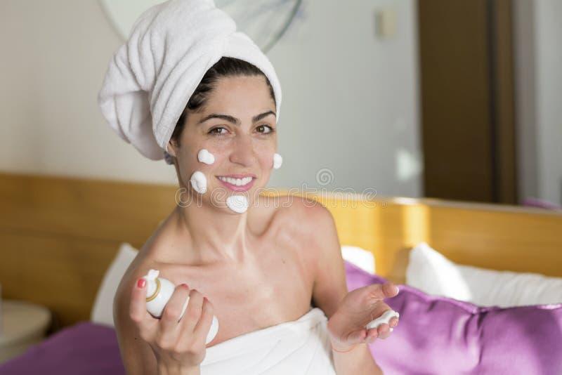 Lachende vrouw met room op haar gezicht royalty-vrije stock fotografie
