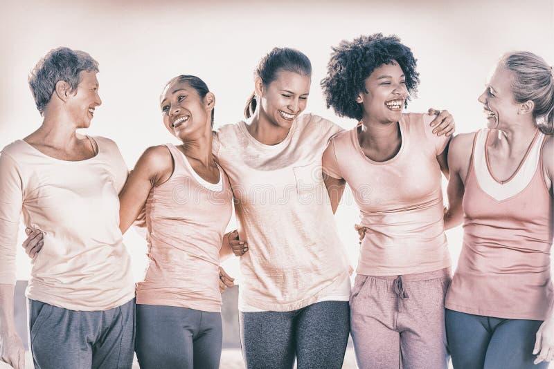 Lachende vrouwen die roze voor borstkanker dragen royalty-vrije stock afbeeldingen