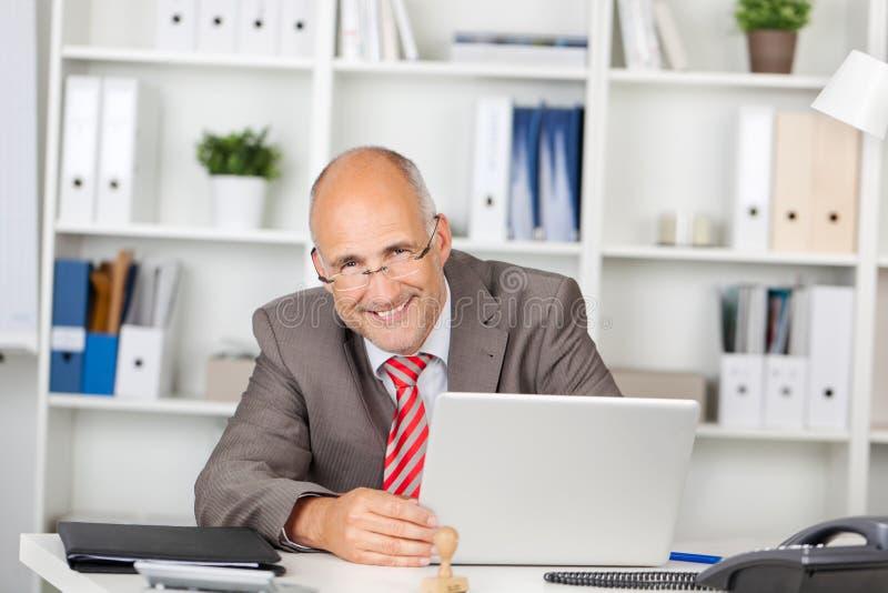 Lachende zakenman met laptop royalty-vrije stock foto's
