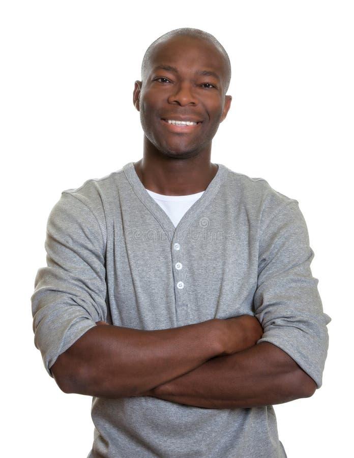 Lachender afrikanischer Mann in einem grauen Hemd mit den gekreuzten Armen lizenzfreie stockfotos