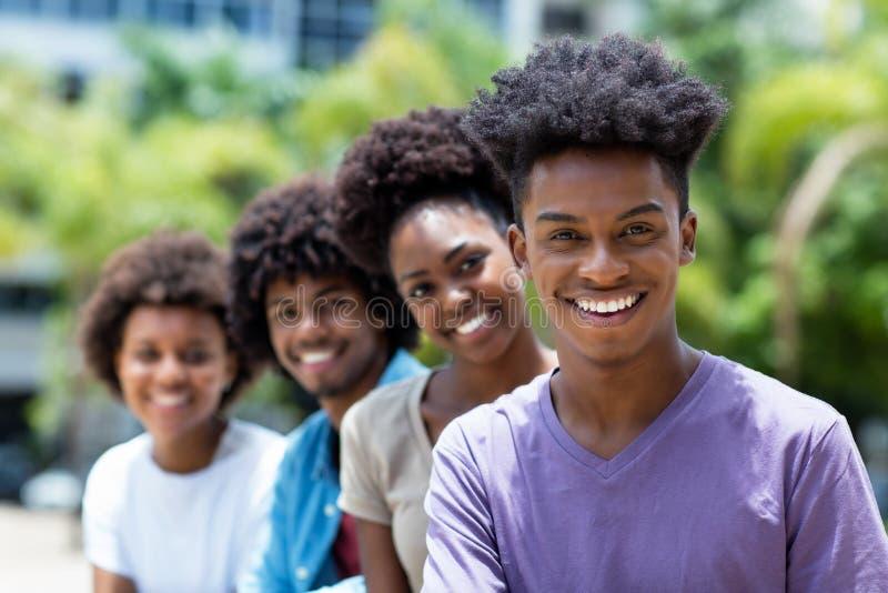 Lachender Afroamerikanermann mit Gruppe jungen Erwachsenen in der Linie stockbild
