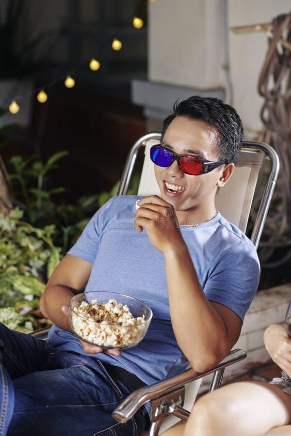 Lachender aufpassender Film des Mannes lizenzfreie stockbilder