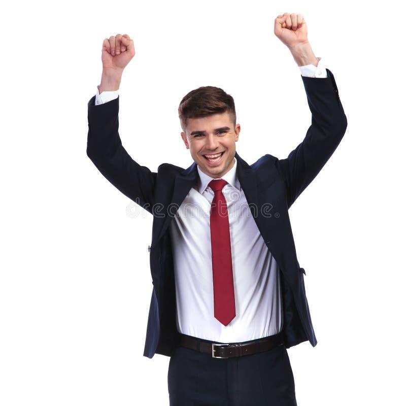 Lachender Geschäftsmann, der Erfolg mit den Fäusten in der Luft feiert stockfoto