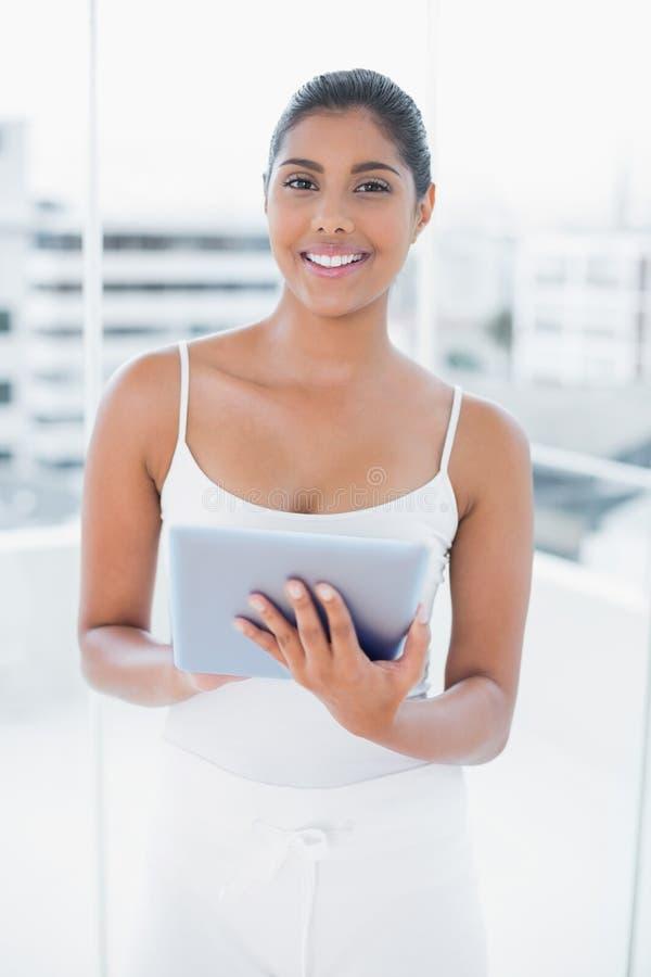 Lachender getonter Brunette, der Tablette verwendet lizenzfreie stockbilder