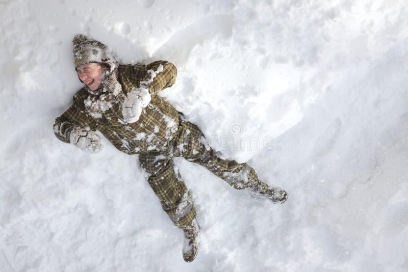 Lachender Junge, der in den Schnee legt stockfotografie