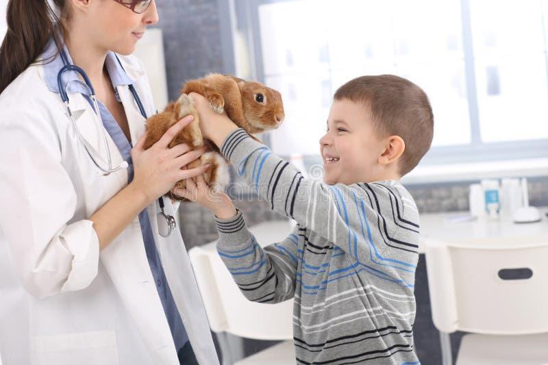 Lachender Junge, der rückseitiges Kaninchen vom Tierarzt erhält stockfoto