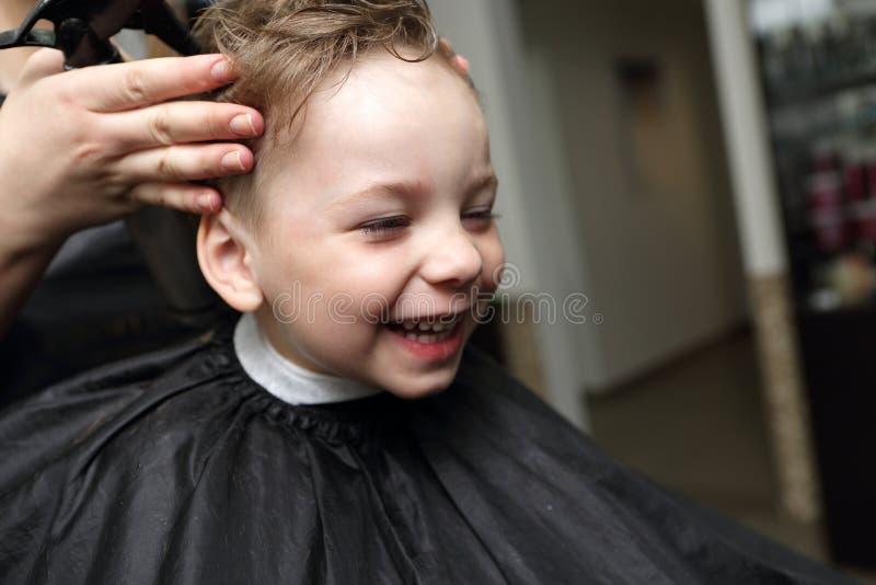 Lachender Junge am Friseursalon stockfotos