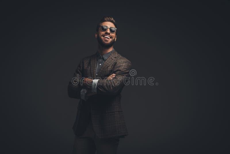 Lachender junger Mann in der Klage und die Sonnenbrille, die mit den Armen steht, kreuzten, stockfotos