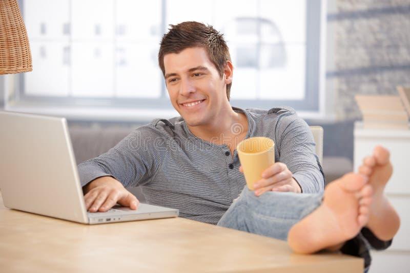 Lachender junger Mann, der zu Hause Computer verwendet