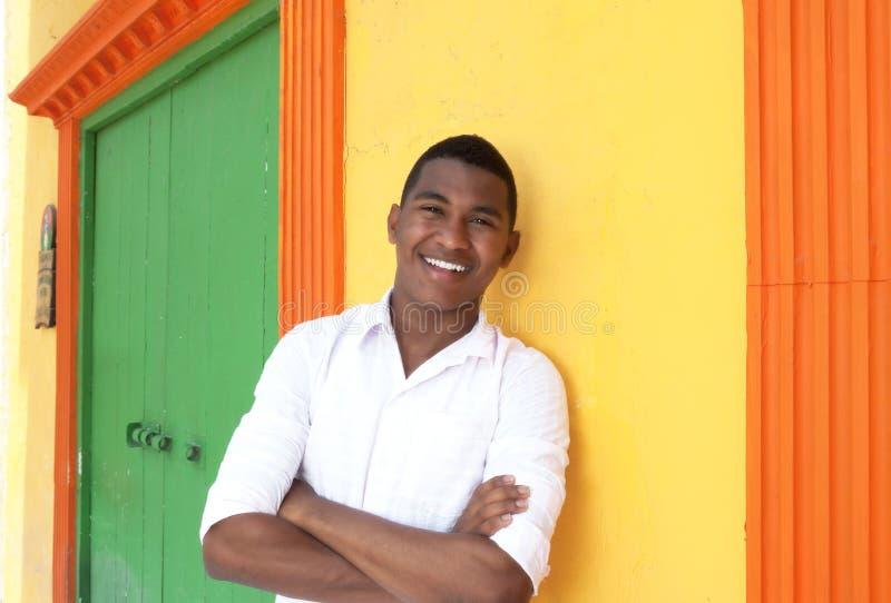 Lachender karibischer Kerl vor einem bunten Haus lizenzfreies stockfoto