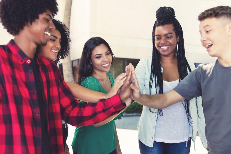 Lachender Latein und Afroamerikanermänner und -frauen, die ein Team errichten stockfoto
