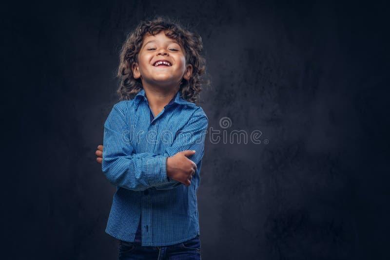 Lachender netter Schüler mit dem braunen gelockten Haar kleidete in einem blauen Hemd an und warf an einem Studio auf auf einem d stockbilder