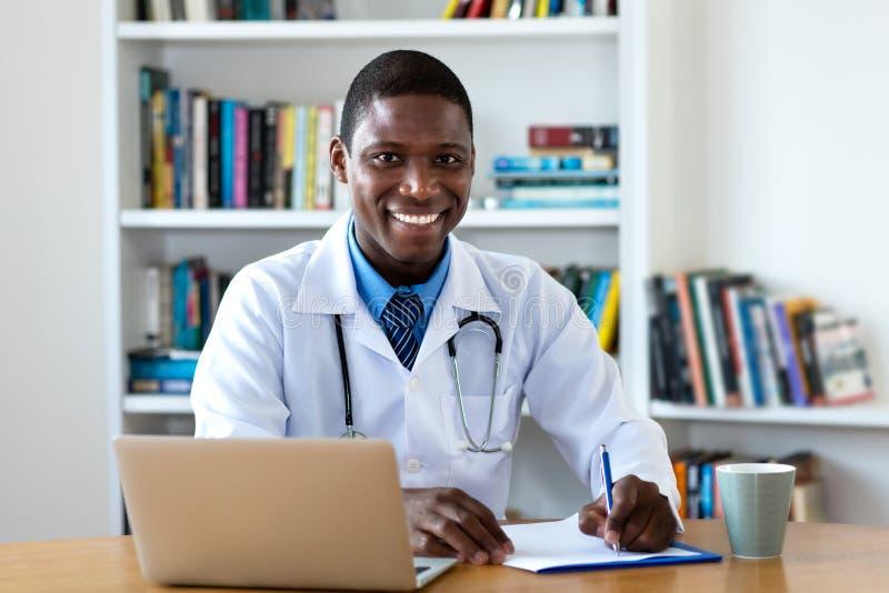 Lachender reifer männlicher Doktor des Afroamerikaners stockfotos