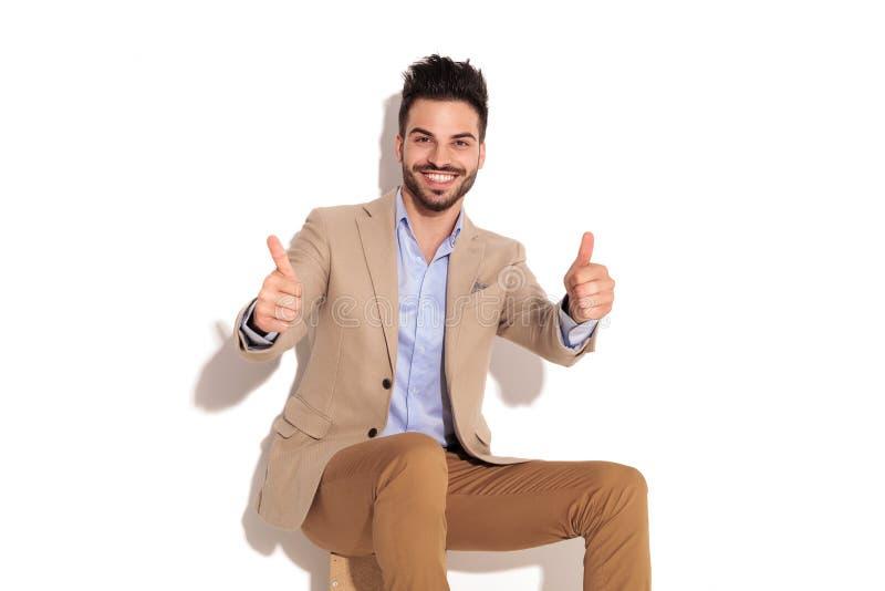 Lachender Sitzgeschäftsmann, der das okayzeichen macht stockfoto