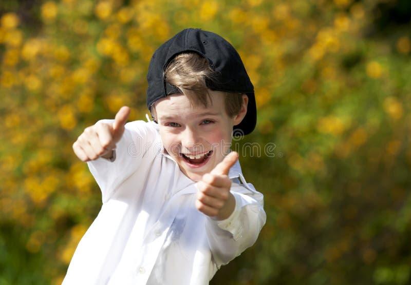 Lachender stattlicher Junge, der oben beide Daumen aufwirft lizenzfreie stockfotografie