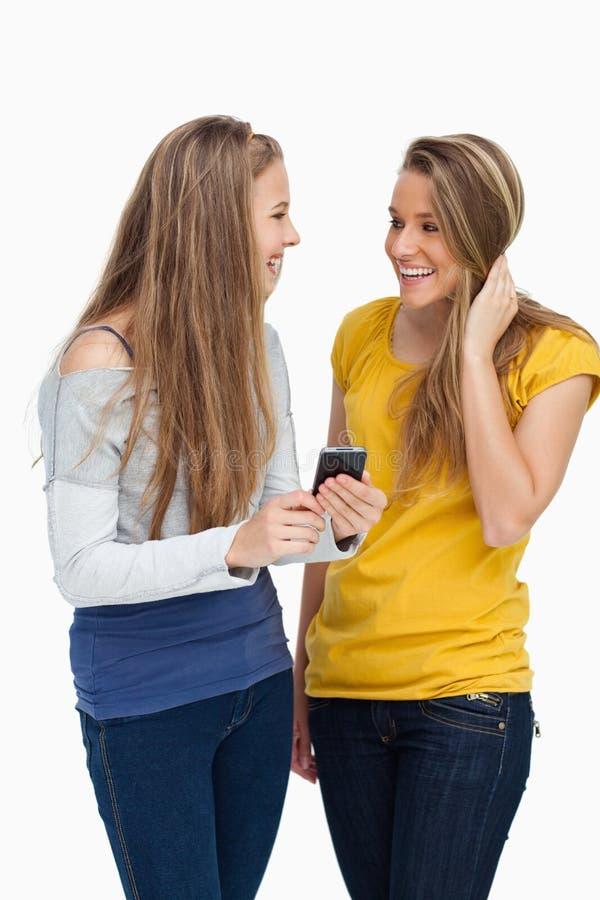 Lachender Student mit zwei Frauen beim Halten eines Mobiltelefons lizenzfreie stockfotografie