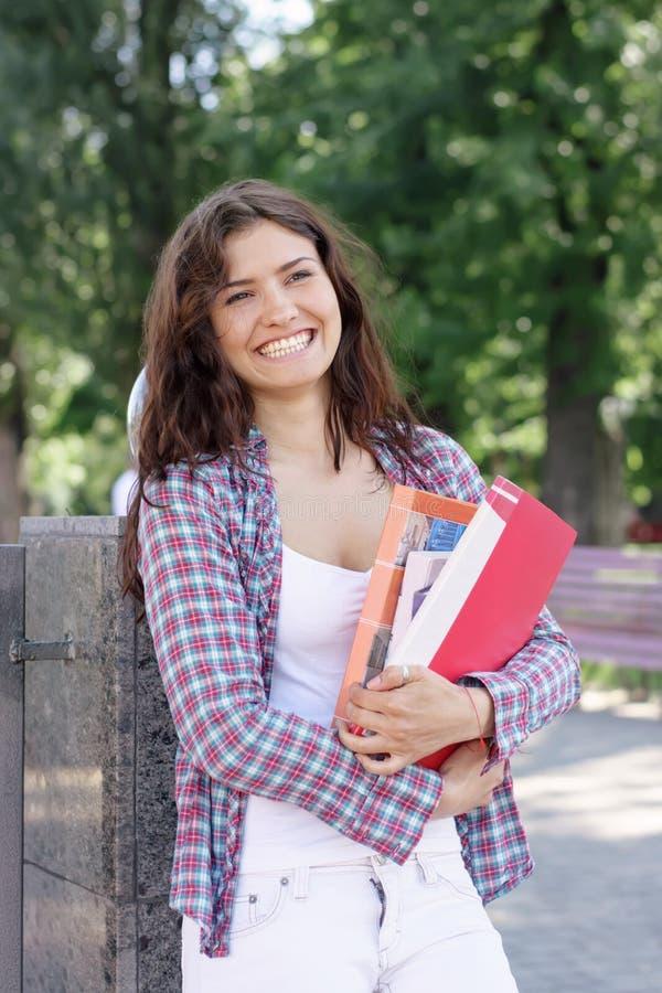 Lachender Studentenspaß beim Halten eines Buches in ihren Händen stockfotografie