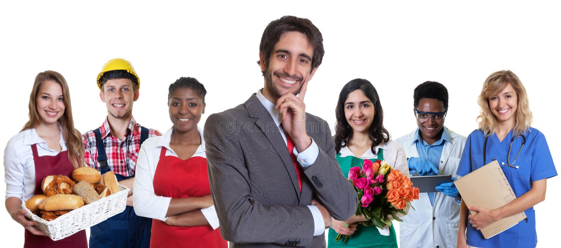 Lachender türkischer Geschäftsauszubildender mit Gruppe lateinischen und afrikanischen Lehrlingen stockbild