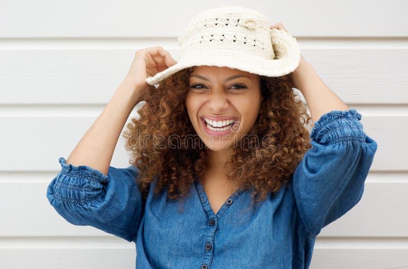 Lachender und tragender Sommerhut der netten sorglosen Frau stockfotografie