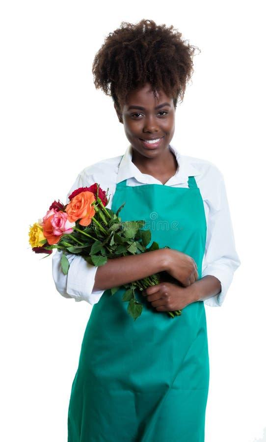 Lachender weiblicher Florist des Afroamerikaners mit dem gelockten Haar und grünem Schutzblech lizenzfreie stockfotografie