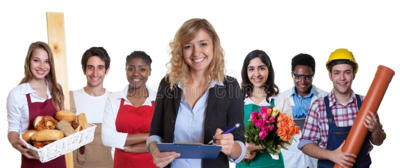 Lachender weiblicher Geschäftsauszubildender mit Gruppe anderer internationaler Lehrlinge lizenzfreie stockfotos