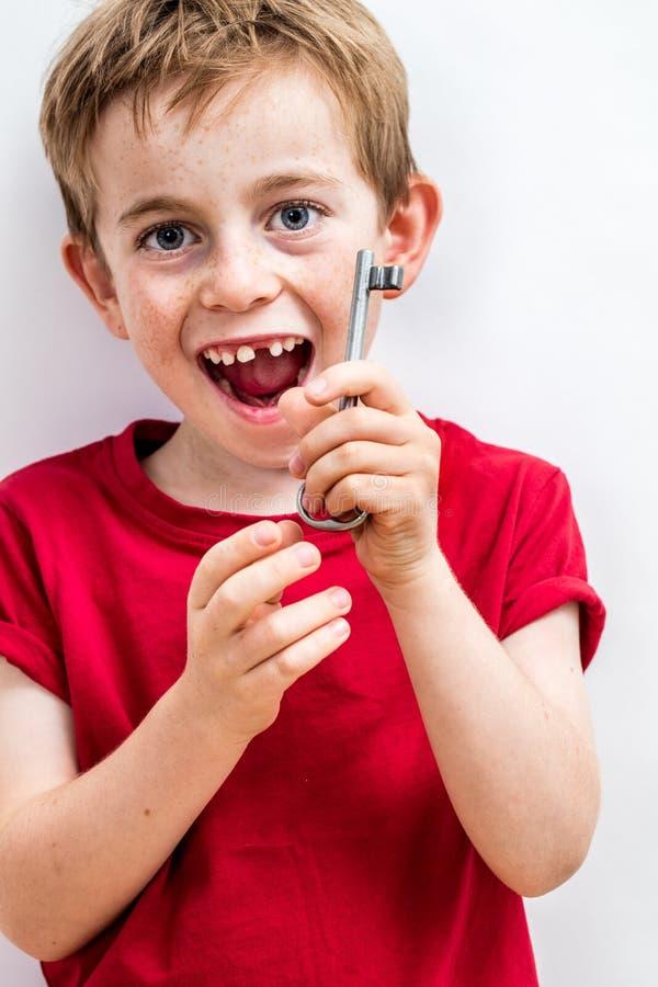Lachender zahnlos netter Junge, der das Halten Schlüssel für boshafte Kreativität genießt lizenzfreie stockfotografie