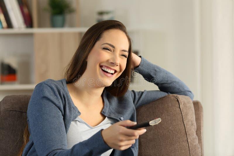 Lachendes aufpassendes Fernsehen des Mädchens auf einer Couch zu Hause stockfoto