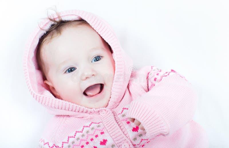 Lachendes Baby, das gestrickte rosa Strickjacke mit roten Herzen trägt lizenzfreie stockbilder
