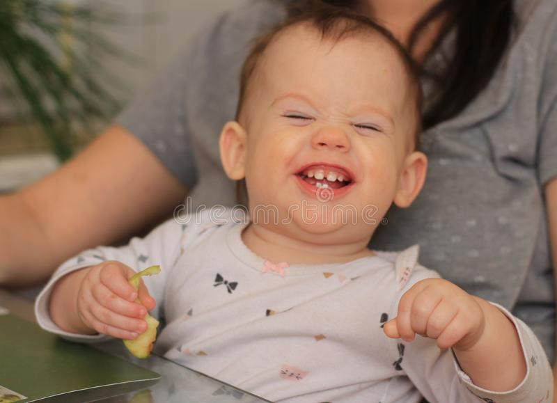 lachendes Baby im mom& x27; s-Arme stockfoto