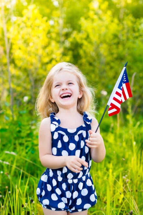 Lachendes blondes kleines Mädchen mit dem gelockten Haar, das amerikanische Flagge hält lizenzfreie stockbilder