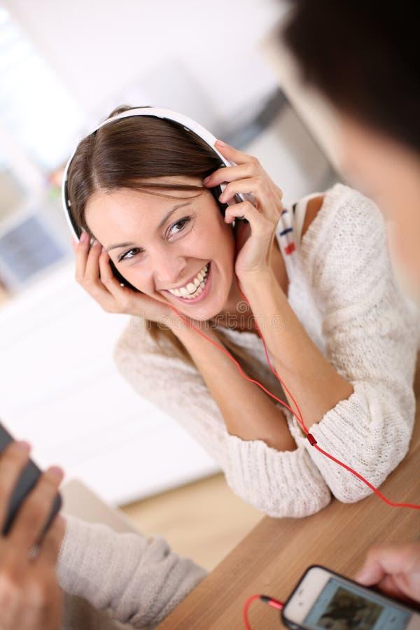 Lachendes Hören der jungen Frau Musik lizenzfreie stockfotografie
