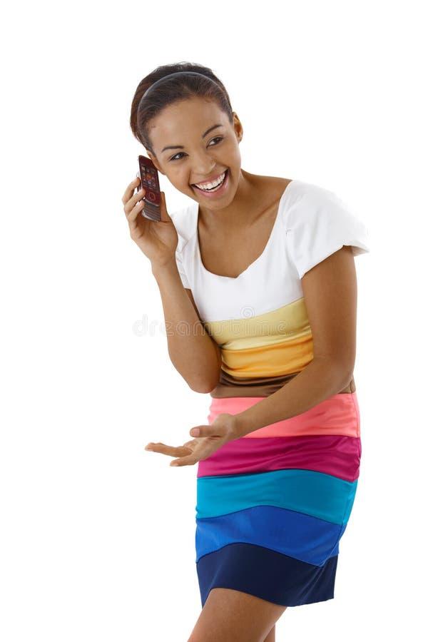 Lachendes hübsches Mädchen beim Telefonaufruf stockbild