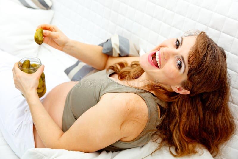 Lachendes Holdingglas der schwangeren Frau Essiggurken stockfoto