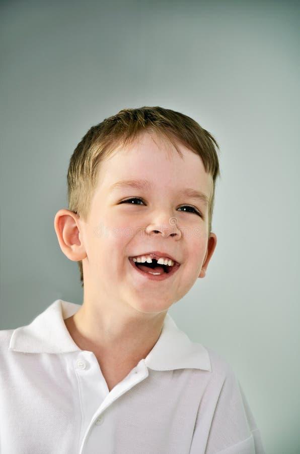 Lachendes Jungenportrait der Junge öffnete seinen Mund und verlor einen Zahn stockfotos
