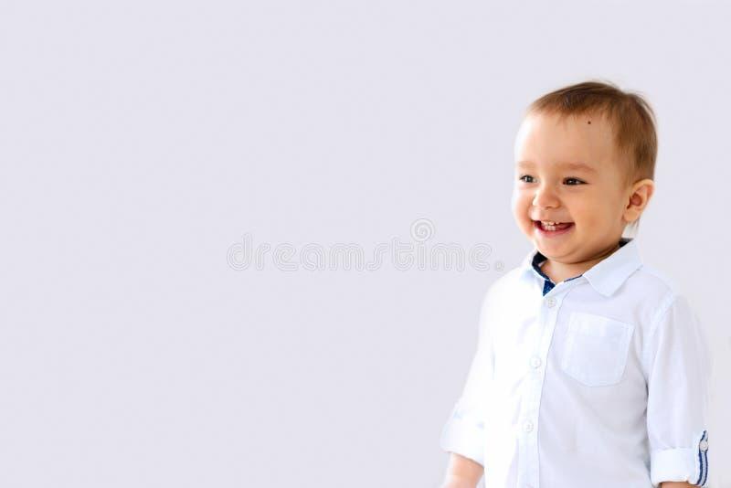 Lachendes Kind in einer weißen Hemdstellung auf einem grauen Hintergrundisolator lizenzfreie stockbilder